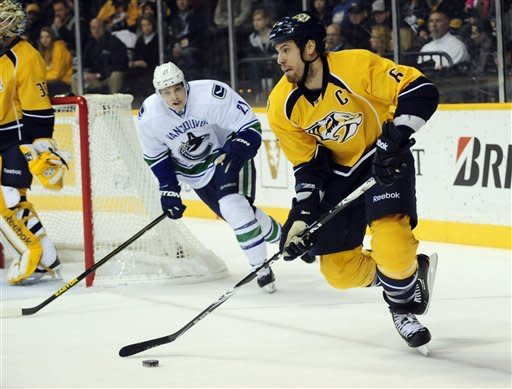 Nashville Predators' Shea Weber (6) brings the puck past Vancouver Canucks' Mason Raymond (21) in the first period of an NHL hockey game on Friday, Feb. 22, 2013, in Nashville, Tenn. (AP Photo/Mike Strasinger)