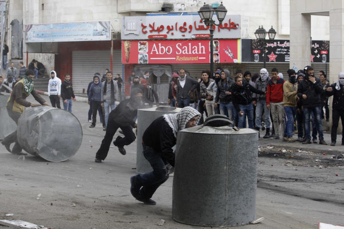 Palestinians take cover behind containers during clashes with Israeli troops in the West Bank city of Hebron, following the death of Arafat Jaradat, a Palestinian prisoner held in Israel jail, Sunday, Feb. 24, 2013. The death of a 30-year-old Palestinian after interrogation by Israel's Shin Bet security service stokes new West Bank clashes, along with Israeli fears of a third Palestinian uprising. (AP Photo/Nasser Shiyoukhi)