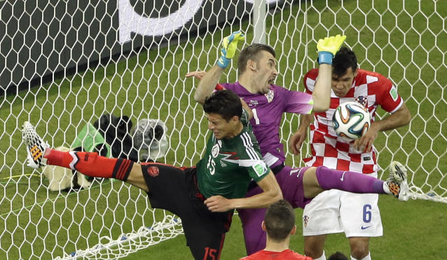 Croatia's goalkeeper Stipe Pletikosa leaps to make a save during the group A World Cup soccer match between Croatia and Mexico at the Arena Pernambuco in Recife, Brazil, Monday, June 23, 2014. Mexico's Hector Morenois at left and Croatia's Dejan Lovren is at right on the play. (AP Photo/Hassan Ammar)