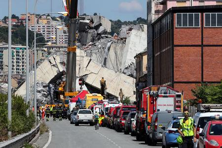 Firefighters and rescue workers stand at the site of a collapsed Morandi Bridge in the port city of Genoa