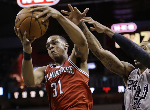 Milwaukee Bucks' John Henson (31) grabs a rebound in front of San Antonio Spurs' Malcolm Brown (24) during the second half of an NBA basketball game, Sunday, Jan. 19, 2014, in San Antonio. San Antonio won 110-82. (AP Photo/Eric Gay)