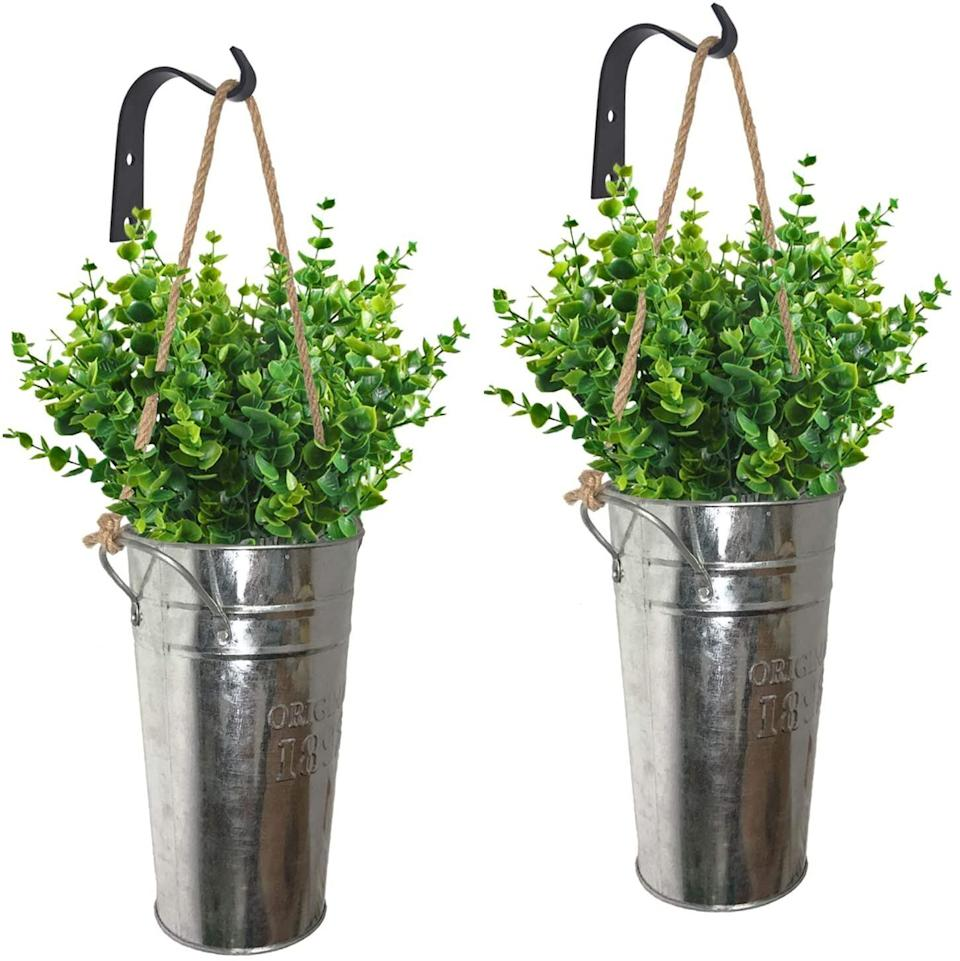 """This set of planters come with atwo galvanized buckets, two hemp ropes and two black metal hooks. You'll just need to add the flowers — either fresh or faux.<a href=""""https://amzn.to/34dUMJk"""" target=""""_blank"""" rel=""""noopener noreferrer"""">Find it for $21 at Amazon</a>."""