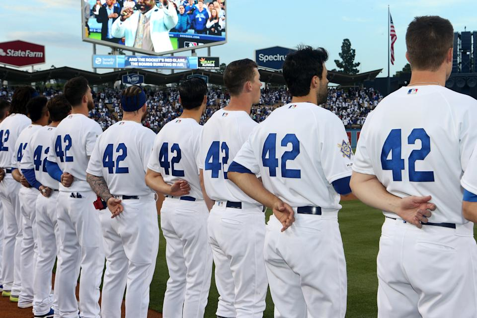 LOS ANGELES, CA - APRIL 15: Members of the Los Angeles Dodgers, wearing #42 for Jackie Robinson Day, stand for the national anthem prior to the game between the Cincinnati Reds and the Los Angeles Dodgers at Dodger Stadium on Monday, April 15, 2019 in Los Angeles, California. (Photo by Rob Leiter/MLB via Getty Images)