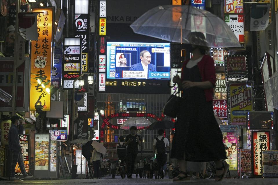 A night time image of people on a rainy street with a large screen in the background.