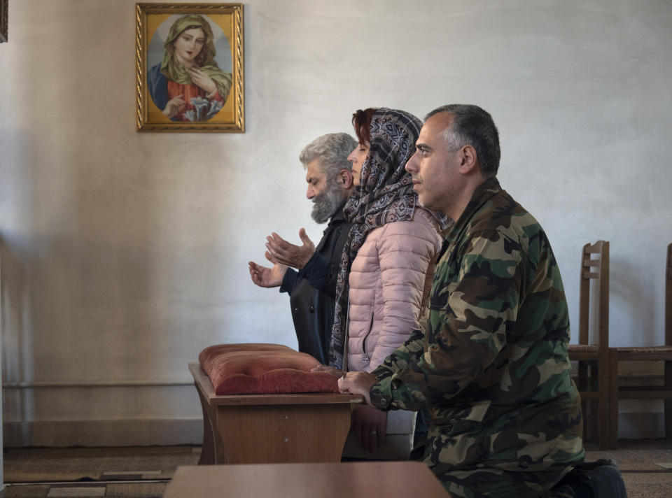 Volunteer doctors Aram Grigoryan, right, and Eleonora Ovanesyan, center pray with a priest in a church during a military conflict in Stepanakert, the separatist region of Nagorno-Karabakh, Friday, Oct. 16, 2020. (AP Photo)