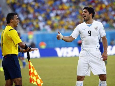 Uruguay's Suarez argues with first assistant referee Torrentera of Mexico during their 2014 World Cup Group D soccer match against Italy at the Dunas arena in Natal