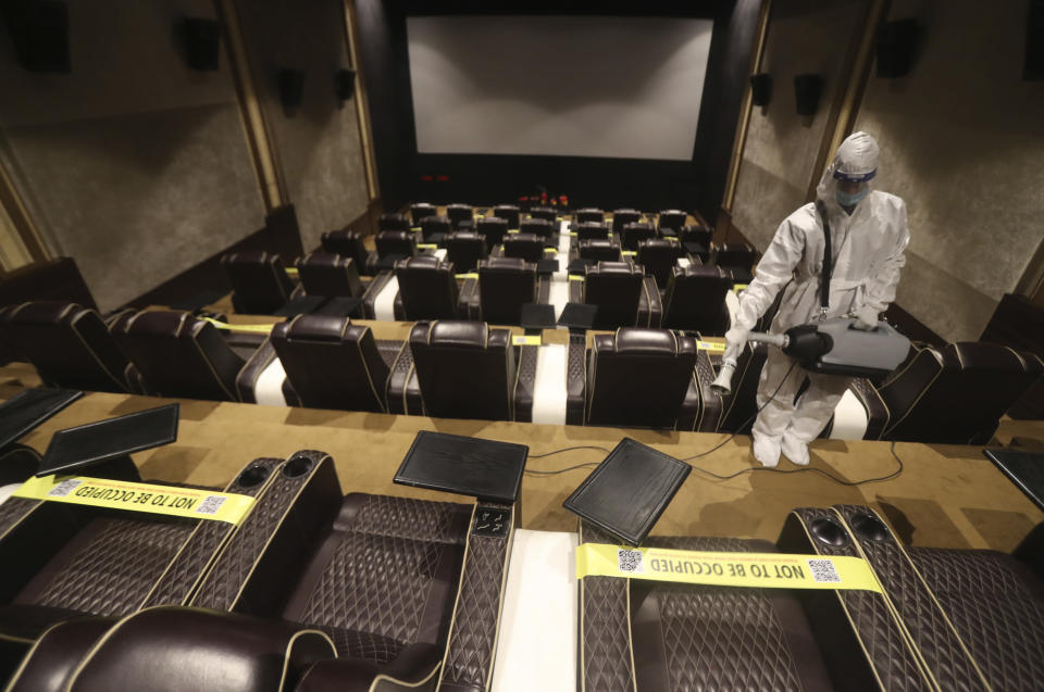 An employee sanitizes a cinema in Mumbai, India, Sunday, Nov. 15, 2020. India is second in the world in total reported coronavirus cases behind the U.S., but daily infections have been on the decline since the middle of September. (AP Photo/Rafiq Maqbool)