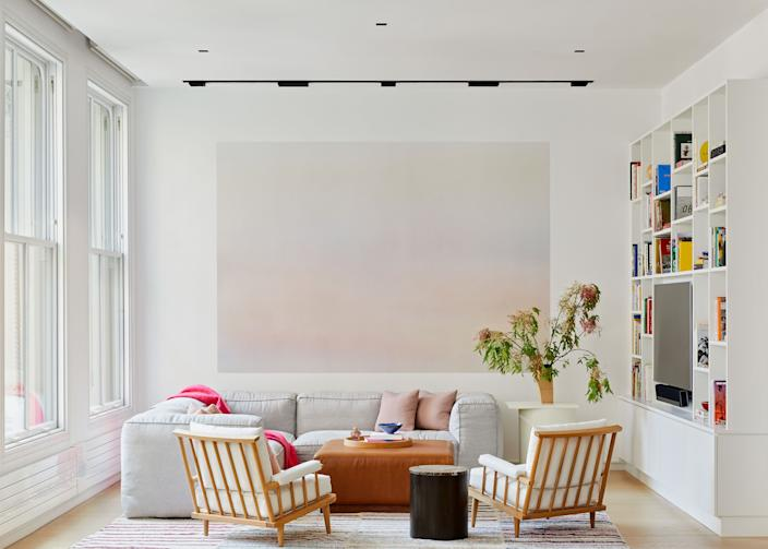 """<div class=""""caption""""> Los Angeles designer Kelly Bergin transformed a bright if blank Tribeca loft into an inviting family home filled with light and soft texture. A painting by French artist Isabelle Cornaro dominates the family library, where an <a href=""""https://www.restorationhardware.com/"""" rel=""""nofollow noopener"""" target=""""_blank"""" data-ylk=""""slk:RH"""" class=""""link rapid-noclick-resp"""">RH</a> sofa, <a href=""""https://nickeykehoe.com/"""" rel=""""nofollow noopener"""" target=""""_blank"""" data-ylk=""""slk:Nickey Kehoe"""" class=""""link rapid-noclick-resp"""">Nickey Kehoe</a> chairs, and a collection of vintage kilims combine to create a cozy reading nook. </div>"""
