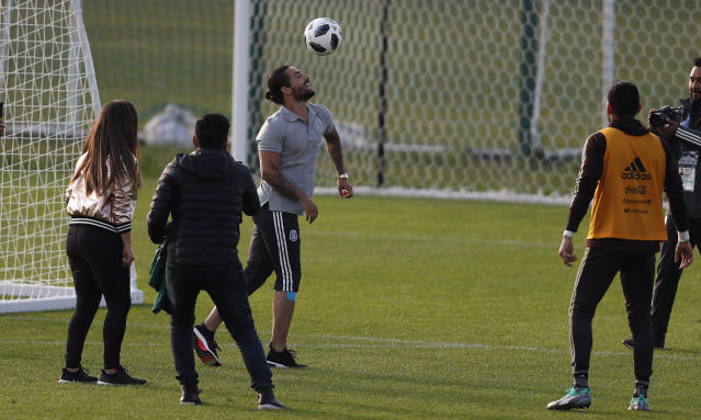 Colombian singer Maluma, left, control the ball next to Mexico goalkeeper Jose de Jesus Corona, right, at the end of a training session of the Mexico national soccer team, for the 2018 soccer World Cup, in Moscow, Russia, Tuesday, June 12, 2018. (AP Photo/Eduardo Verdugo)