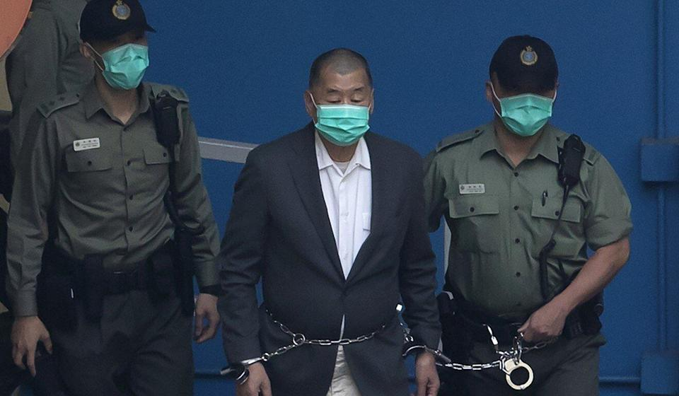 Jimmy Lai who founded the Apple Daily, is escorted by Correctional Services officers in December 2020 before appearing in a court in Hong Kong. Photo: AP