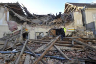 People walk through the rubble from buildings damaged in an earthquake in Petrinja, Croatia, Tuesday, Dec. 29, 2020. A strong earthquake has hit central Croatia and caused major damage and at least one death and some 20 injuries in the town southeast of the capital Zagreb. (AP Photo)