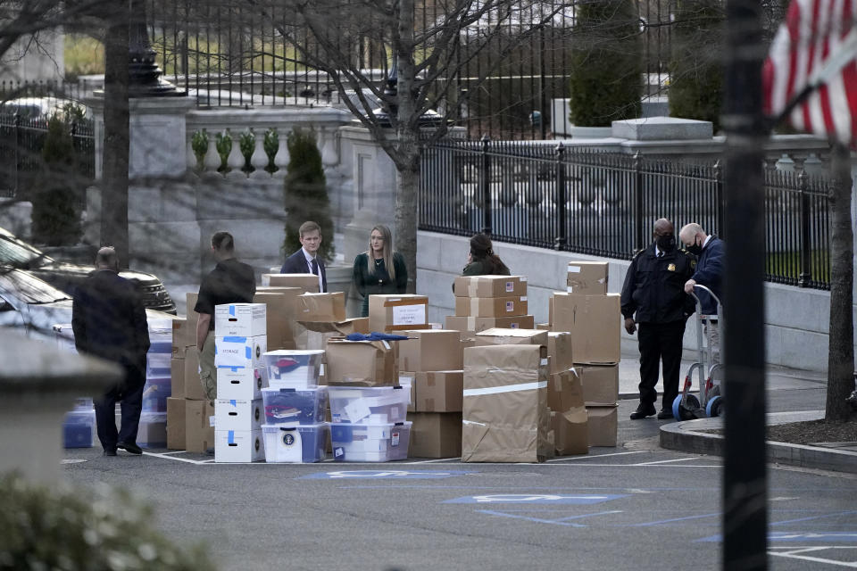 FILE - In this Jan. 14, 2021, file photo people wait for a moving van after boxes were moved out of the Eisenhower Executive Office building inside the White House complex in Washington. The public won't see President Donald Trump's White House records for years, but there's growing concern that they won't be complete, leaving a hole in the history of one of America's most tumultuous presidencies. (AP Photo/Gerald Herbert, File)