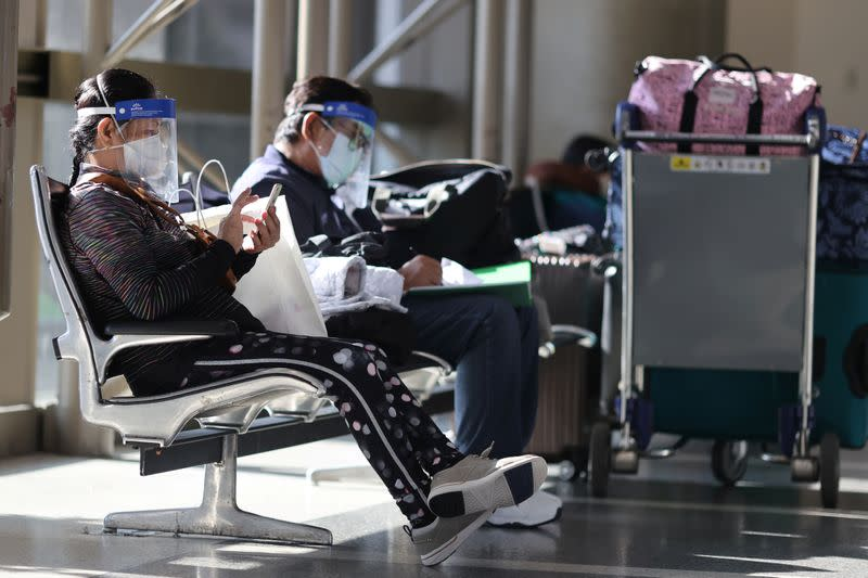 Passengers wear masks as they sit in the departures area, amid the global outbreak of the coronavirus disease (COVID-19), at the Tom Bradley International terminal of the LAX airport in Los Angeles