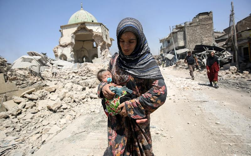 An Iraqi woman, carrying an infant, walks in the Old City of Mosul on July 5, 2017 during the government offensive against the Islamic State group