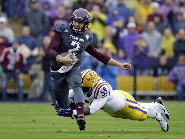 FILE - In this Nov. 23, 2013, file photo, Texas A&M quarterback Johnny Manziel (2) scrambles to avoid a tackle by LSU defensive end Jermauria Rasco (59) during the first half of an NCAA college football game in Baton Rouge, La. Manziel could be the answer to Cleveland's prayers at quarterback. The polarizing and popular Texas A&M star will likely be available when the Browns pick fourth in next week's NFL draft. But can they handle the Johnny Football Circus? (AP Photo/Gerald Herbert, File)