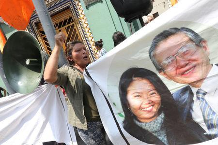 Supporters of opposition leader Keiko Fujimori hold a picture of her and her father, former President Alberto Fujimori, as they wait outside court where she is attending a hearing, in Lima, Peru October 31, 2018. REUTERS/Mariana Bazo