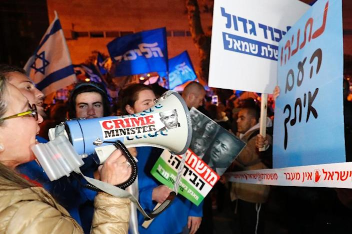 Rival Israeli demonstrators for and against the deeply polarising prime minister square off in Tel Aviv, separated by police (AFP Photo/JACK GUEZ)