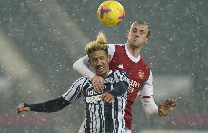 West Bromwich Albion's Callum Robinson, front, vies for the ball with Arsenal's Rob Holding during the English Premier League soccer match between West Bromwich Albion and Arsenal at the Hawthorns in Birmingham, England, Saturday, Jan. 2, 2021. (Tim Keeton/ Pool via AP)