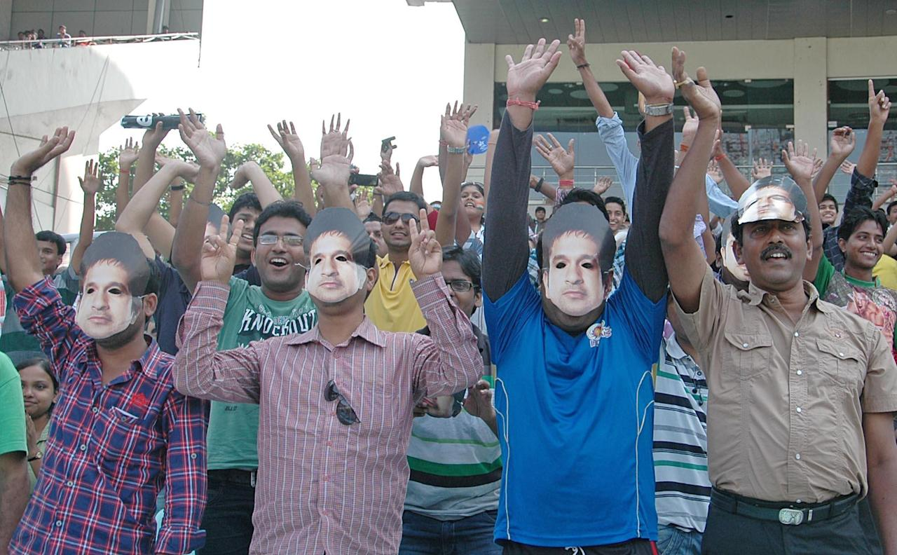 Sachin Tendulkar fans hold his masks during the 3rd day of the 1st test match between India and West Indies at Eden Gardens, Kolkata on Nov. 8, 2013. (Photo: IANS)