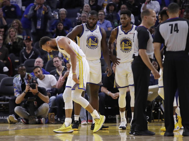 Golden State Warriors' Stephen Curry, left, grimaces after Phoenix Suns' Aron Baynes fell onto him during the second half of an NBA basketball game Wednesday, Oct. 30, 2019, in San Francisco. Curry left the game. (AP Photo/Ben Margot)