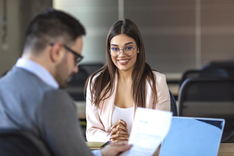 Business, career and placement concept - young woman smiling and holding resume while sitting in front of mentor or managers during job interview. Smiling female client talking to male manager