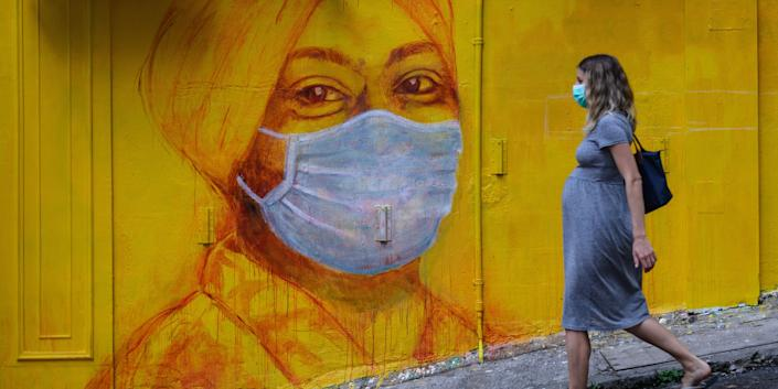 A pregnant woman wearing a face mask walks past a mural in Hong Kong on March 23, 2020.