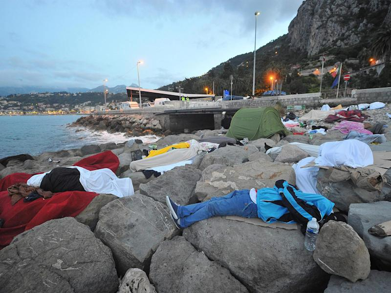 Migrants sleep by the sea yesterday in Ventimiglia, Italy, near the French border, which they have been barred from crossing: EPA