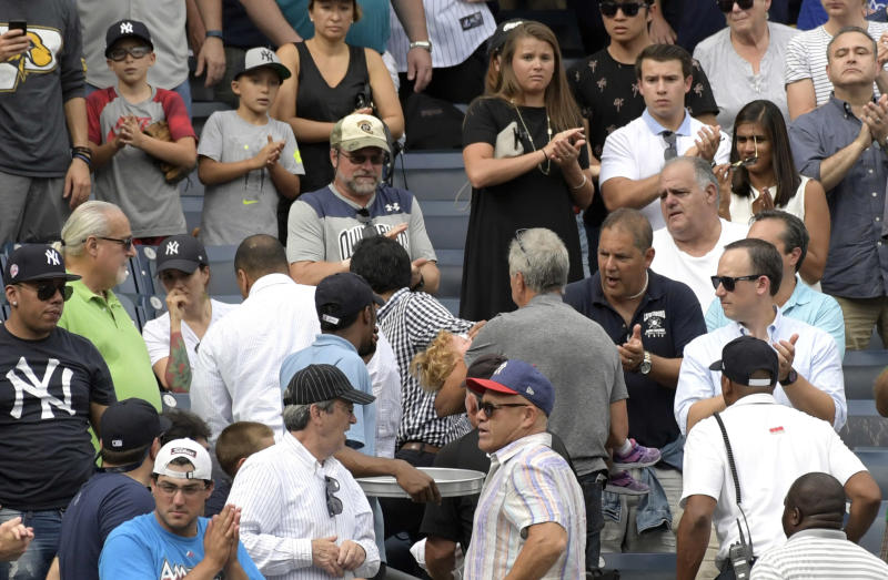 A young girl is carried out of Yankee Stadium after getting hit by a foul ball Wednesday. (AP)