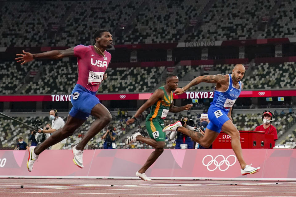Lamont Jacobs, right, of Italy, wins the men's the 100-meter final at the 2020 Summer Olympics, Sunday, Aug. 1, 2021, in Tokyo. (AP Photo/David J. Phillip)