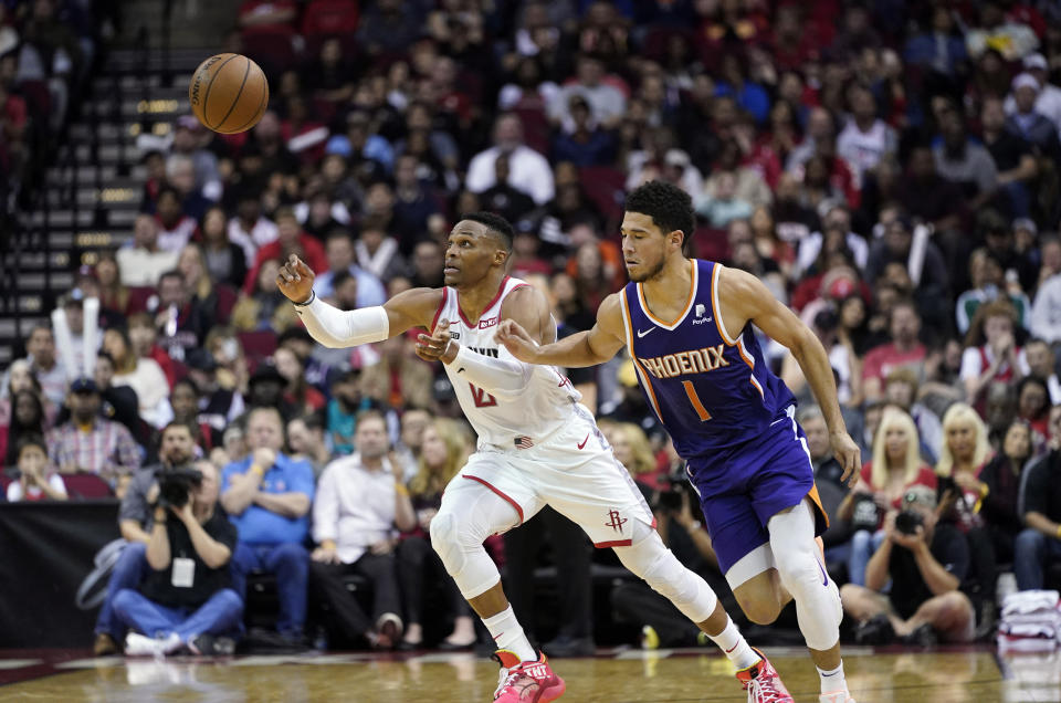 Houston Rockets' Russell Westbrook (0) and Phoenix Suns' Devin Booker (1) reach for a loose ball during the first half of an NBA basketball game Saturday, Dec. 7, 2019, in Houston. (AP Photo/David J. Phillip)