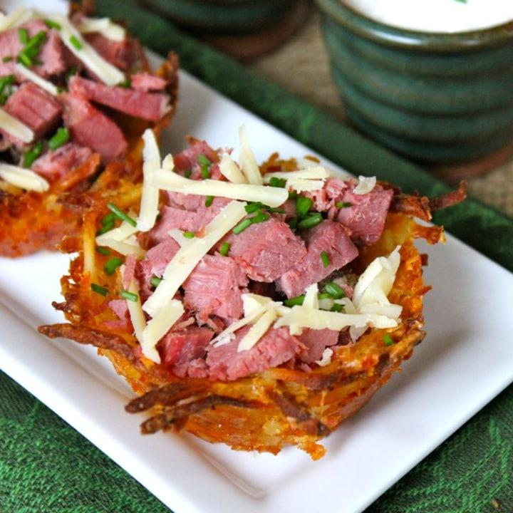 Crispy potato cups cradle shredded corned beef and Irish cheddar cheese in this recipe.