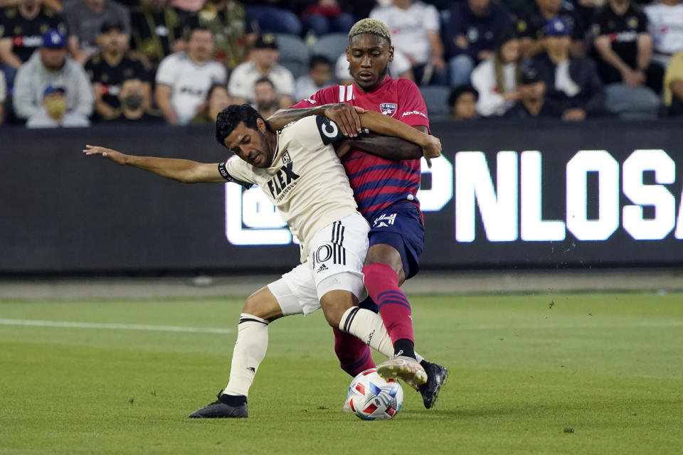 Los Angeles FC forward Carlos Vela, left, is defended by Dallas FC defender Nkosi Burgess during the first half of an MLS soccer match Wednesday, June 23, 2021, in Los Angeles. (AP Photo/Marcio Jose Sanchez)
