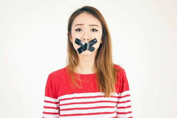 A young woman with tape on her mouth.