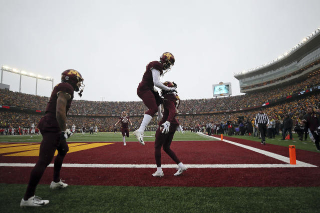 Minnesota wide receiver Tyler Johnson (6) jumps up in the air to celebrate with teammate wide receiver Rashod Bateman (13) after Bateman scored a touchdown against Wisconsin during an NCAA college football game Saturday, Nov. 30, 2019, in Minneapolis. (AP Photo/Stacy Bengs)