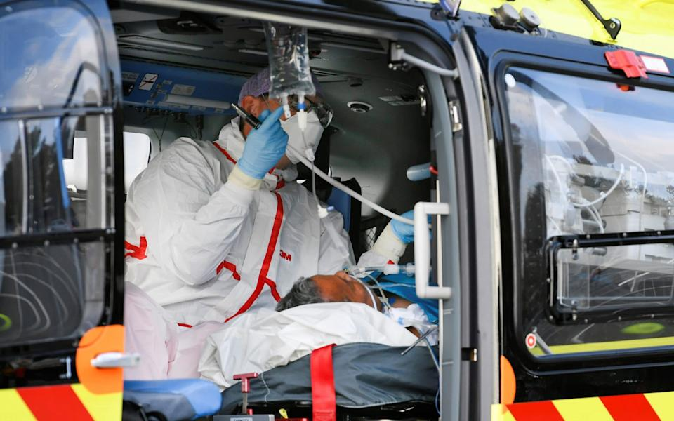 A medical worker prepares aboard a trauma helicopter transferring a patient infected with Covid-19 from the Flevo Hospital in Holland to Germany, where hospitals are helping by taking over Dutch coronavirus patients - REUTERS/Piroschka van de Wouw