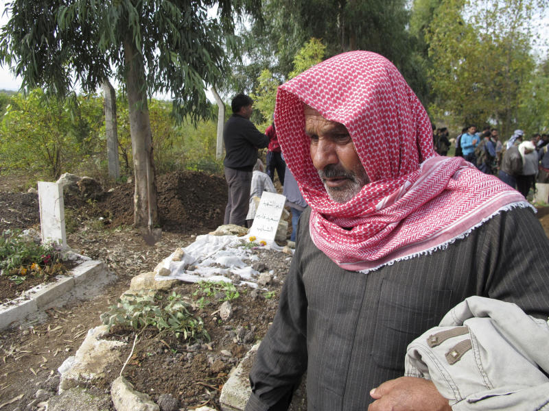 In this Saturday, Nov. 17, 2012 photo, Syrian Mohammed Quweiri, 63, stands near the grave of his son and others killed in fighting between rebels and the Syrian army in Harem, Syria. A dark realization is spreading across north Syria that despite 20 months of violence and recent rebel gains, an end to the war to topple President Bashar Assad is nowhere in sight. (AP Photo/ Ben Hubbard)
