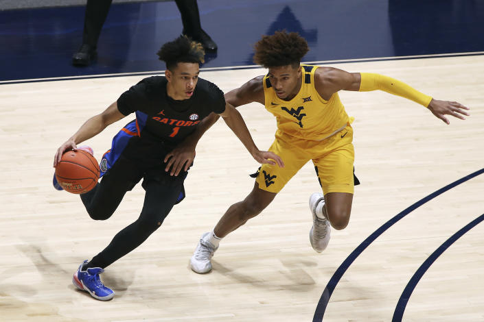 Florida guard Tre Mann (1) is defended by West Virginia guard Miles McBride (4) during the first half of an NCAA college basketball game Saturday, Jan. 30, 2021, in Morgantown, W.Va. (AP Photo/Kathleen Batten)