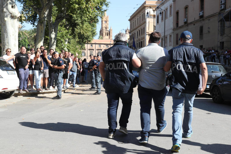 Suspect Antonino Fanara, center, is taken into custody during an anti-mafia operation lead by the Italian Police and the FBI in Palermo, Southern Italy, Wednesday, July 17, 2019. Italian police and the FBI arrested 19 suspected Mafiosi in a joint operation Wednesday following an investigation which revealed alleged ties between Sicily's Cosa Nostra Mafia and New York's Gambino crime family. (Igor Petix/ANSA Via AP)