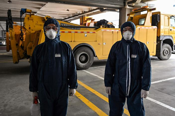 Image: Workers wearing protective gear prepare to disinfect a bus as part of measures against of the COVID-19 coronavirus in Shanghai (Hector Retamal / AFP - Getty Images)