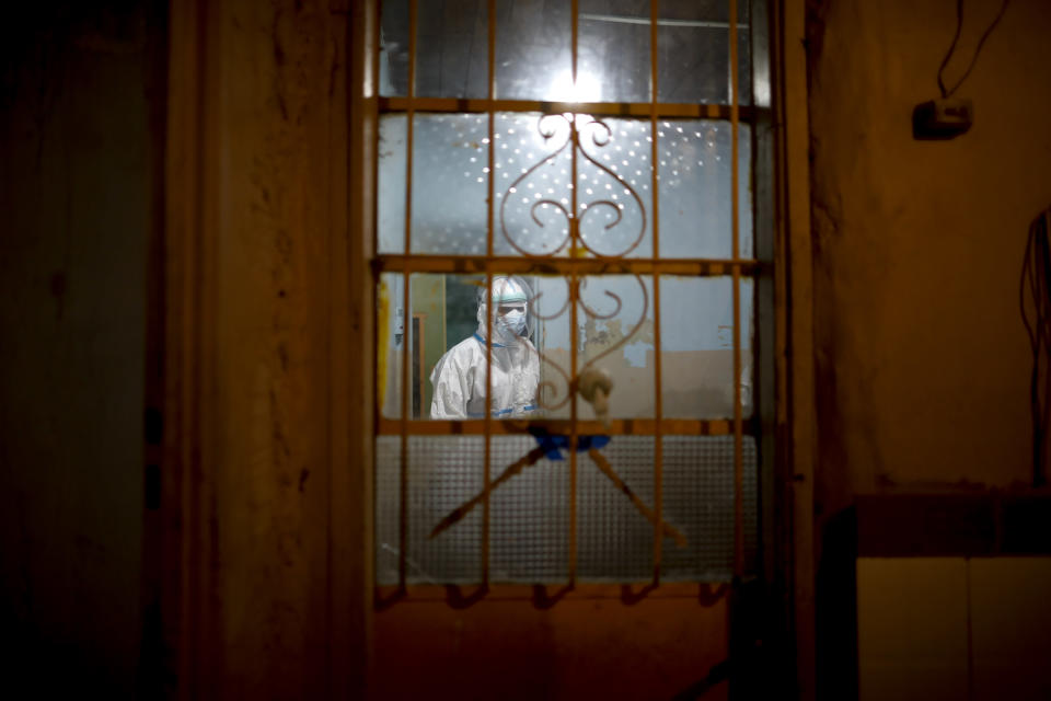 Ambulance Doctor Vladimir Canal enters a home to attend a COVID-19 patient with oxygen problems after an emergency call to the residence during his night shift in Lomas de Zamora, Argentina, late Thursday, June 10, 2021. (AP Photo/Natacha Pisarenko)