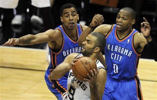 San Antonio Spurs point guard Tony Parker (9), of France, drives to the basket as Oklahoma City Thunder's Thabo Sefolosha, left, of Switzerland, and Russell Westbrook (0) defend during the first quarter of Game 1 in their NBA basketball Western Conference finals playoff series, Sunday, May 27, 2012, in San Antonio. (AP Photo/Darren Abate)