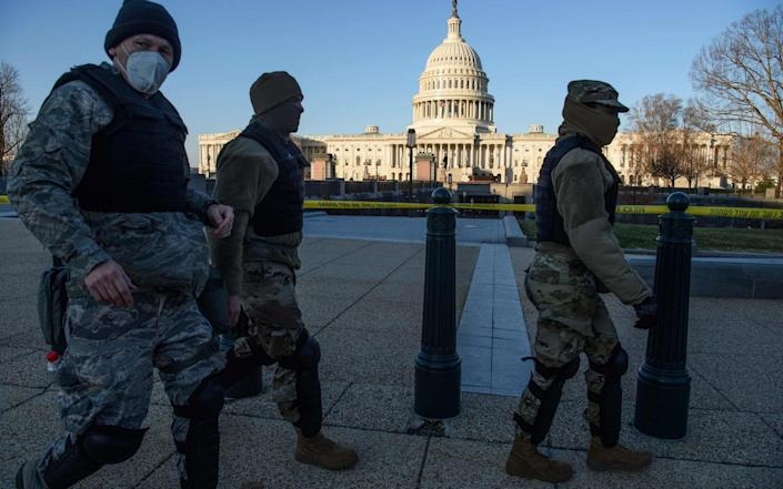 Members of the DC National Guard walk past the US Capitol in Washington, DC - Nicholas Kamim/AFP