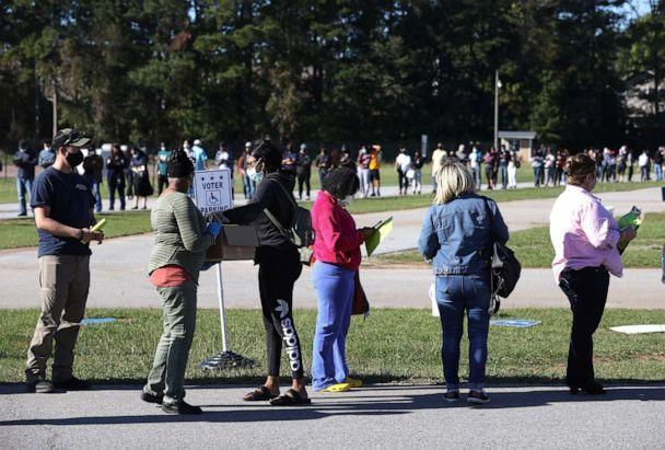 PHOTO: A poll worker hands out pens and clipboards to fill out registration cards as people stand in line to vote at the Gwinnett County Fairgrounds on Oct. 30, 2020, in Lawrenceville, Ga. (Justin Sullivan/Getty Images, FILE)