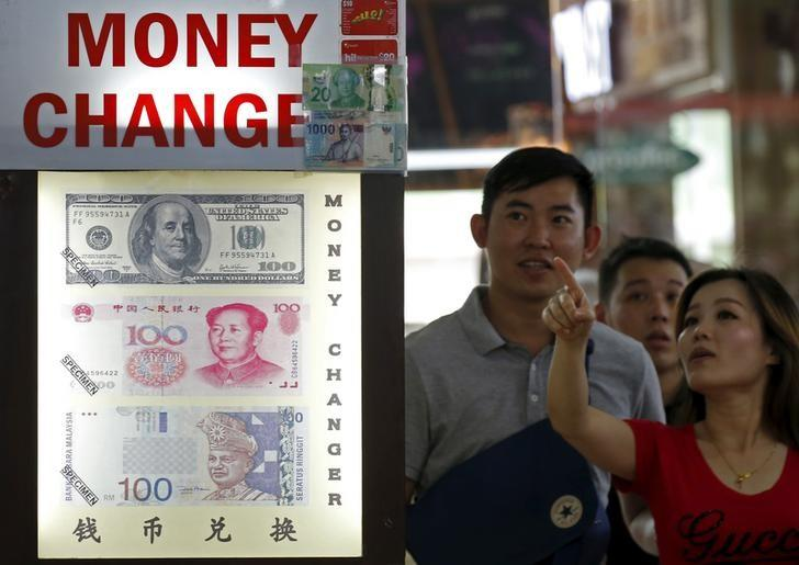 People look at the exchange rate at a Moneychanger displaying posters of U.S. dollars, Chinese Yuan and Malaysia Ringgit in Singapore