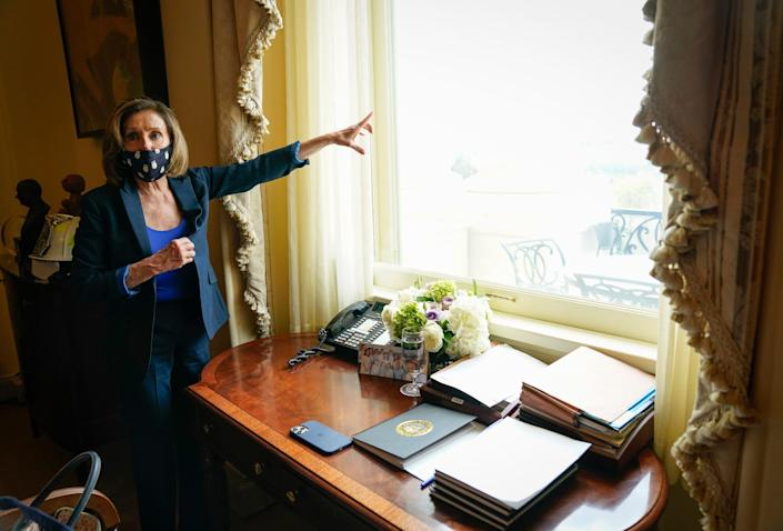 House Speaker Nancy Pelosi, D-Calif., looks out of her Capitol office window at the National Mall on Tuesday.