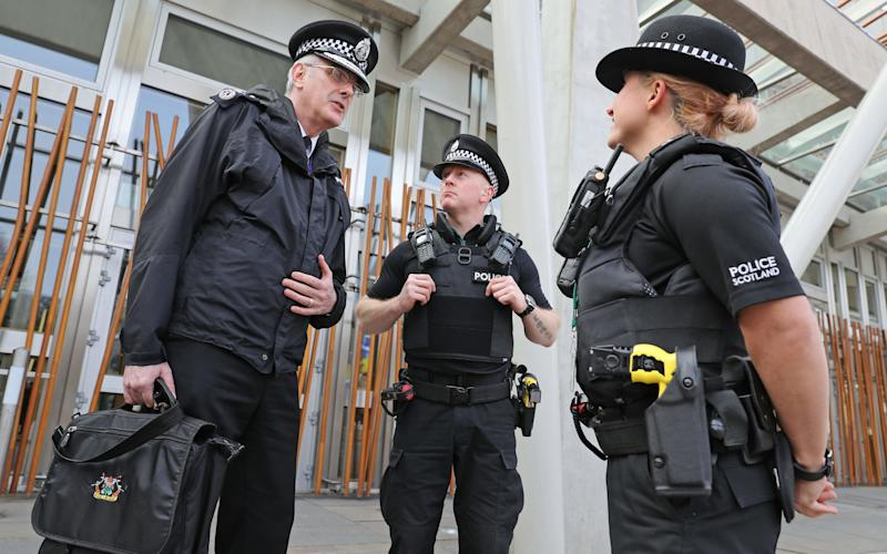 Chief Constable Phil Gormley talks with police officers armed with Tasers outside the Scottish Parliament - PA