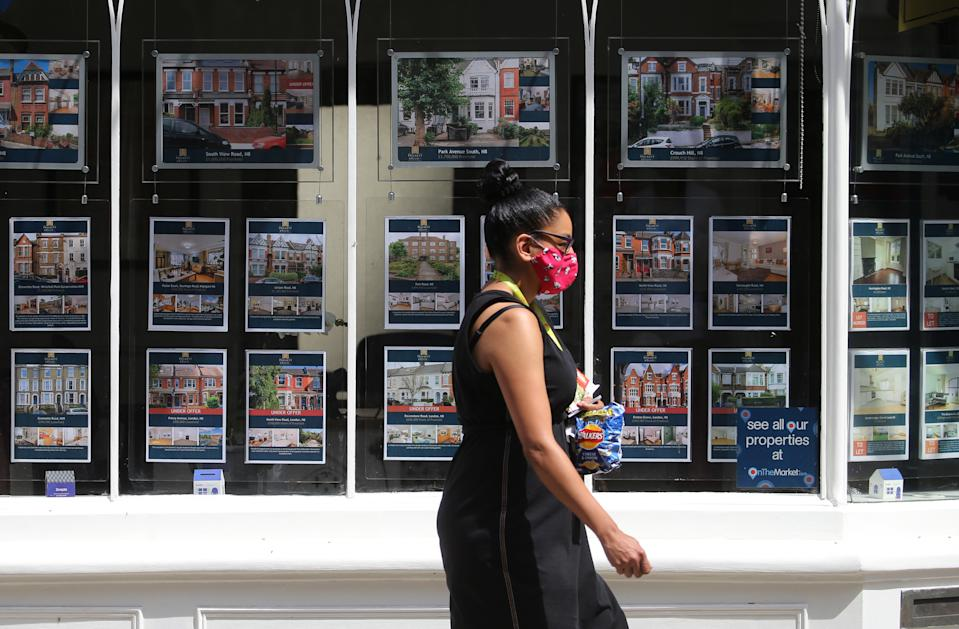 A woman wearing a protective face mask passes an estate agents window in north London. Chancellor Rishi Sunak has confirmed temporary plans to abolish stamp duty on properties up to 500,000 GBP in England and Northern Ireland as part of a package to dull the economic impact of the coronavirus. Picture date: Sunday July 12, 2020.
