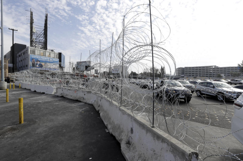 Cars lined up to cross into the United States from Tijuana, Mexico, are seen through barriers topped with concertina wire at the San Ysidro port of entry. Thieves have been taking the wire and selling it in Tijuana for home security. (Gregory Bull/ASSOCIATED PRESS)
