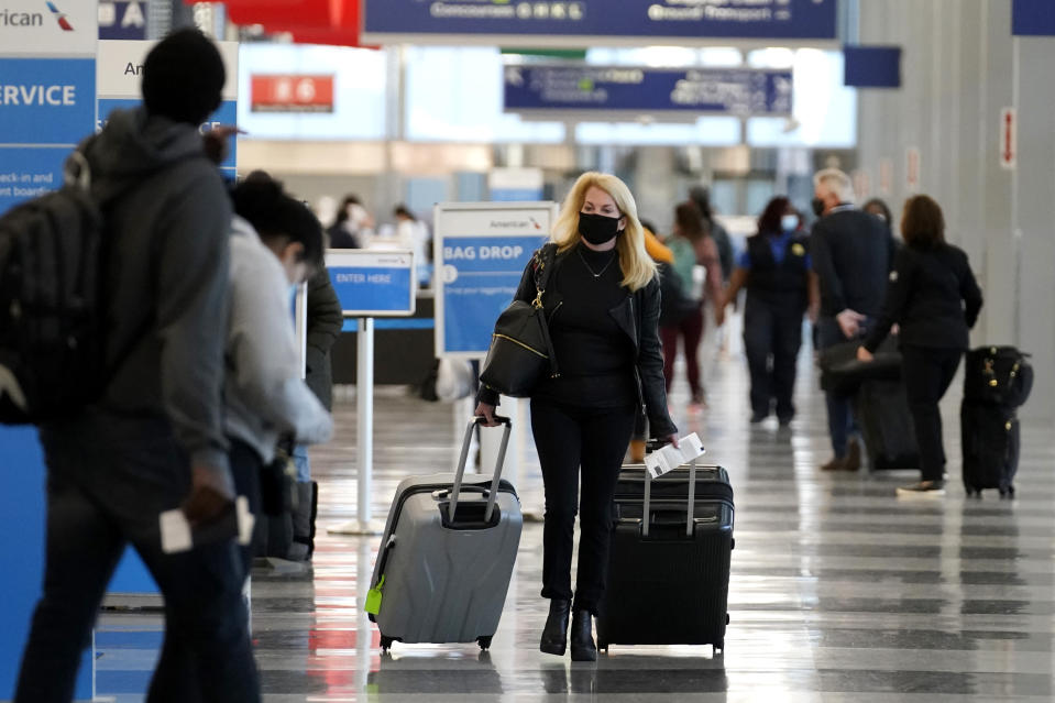 FILE - In this Sunday, Nov. 29, 2020 file photo, a traveler wears a mask as she walks through Terminal 3 at O'Hare International Airport in Chicago. The Transportation Security Administration said nearly 1.2 million people went through U.S. airports on Sunday, the highest number since the coronavirus pandemic gripped the country back in March, despite the pleadings of public health experts for people to stay home over Thanksgiving. (AP Photo/Nam Y. Huh, File)