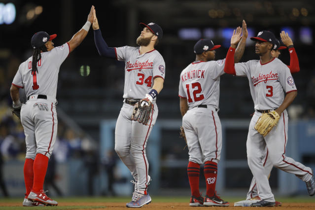 Washington Nationals' Wilmer Difo, Bryce Harper, Howie Kendrick and Michael Taylor, from left, celebrate thei team's 5-2 win against the Los Angeles Dodgers in a baseball game Friday, April 20, 2018, in Los Angeles. (AP Photo/Jae C. Hong)